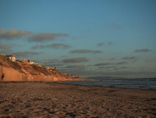 Fim de tarde com por do sol em praia com falésias e casas Solana Tide Beach