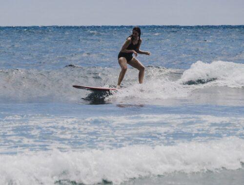 Menina surfando de longboard na prada de Encinitas em San Diego