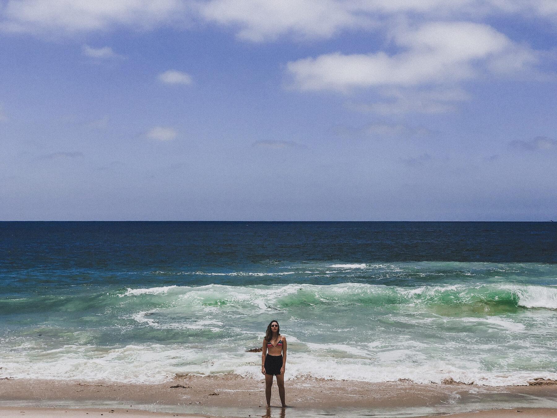 Mulher com os pés na água em Laguna Beach