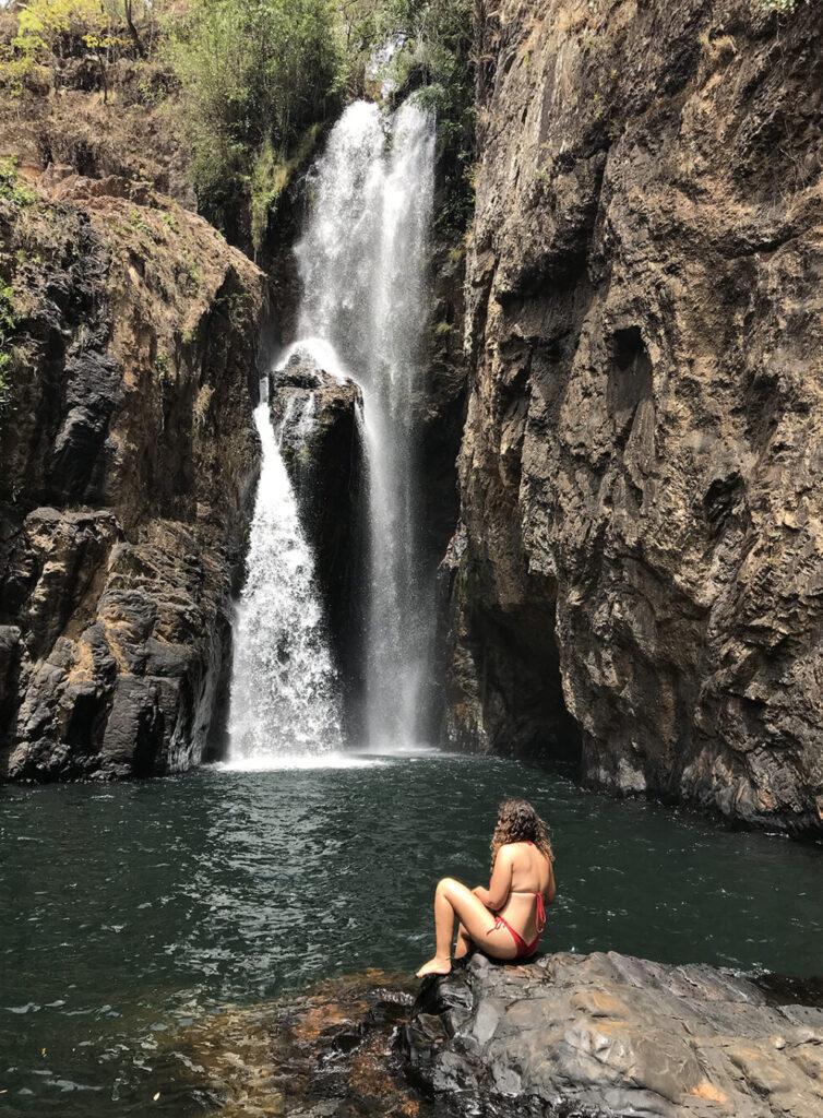 Mulher na pedra em frente a cachoeira do encontro no complexo de macaquinhos chapada dos veadeiros