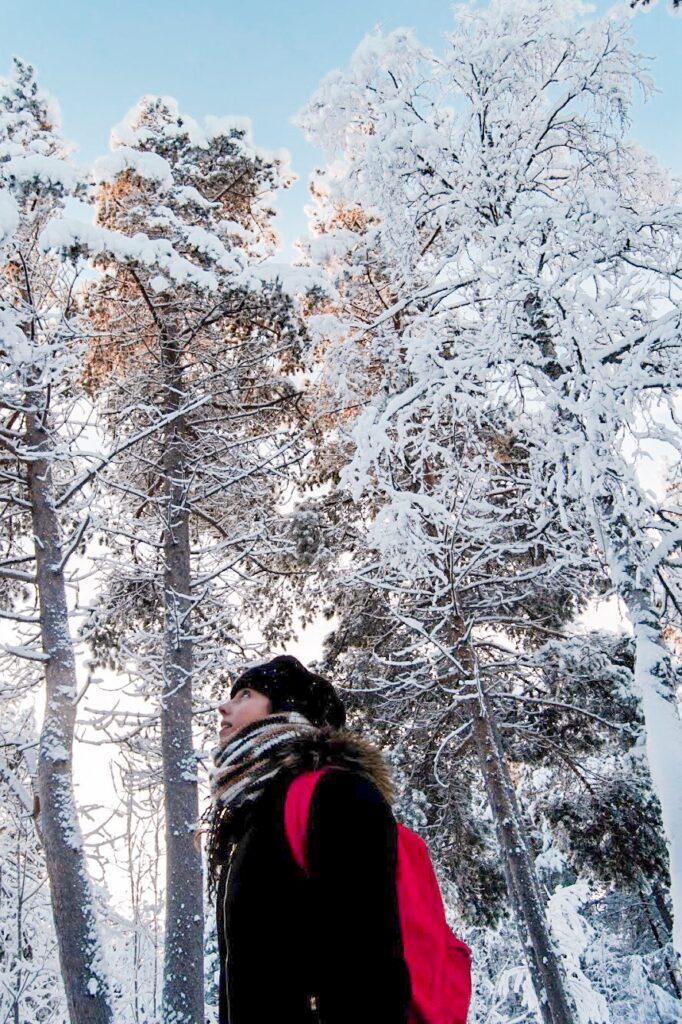 Mulher na neve Inverno Finlândia, inari, com arvores cobertas de neve, mochila vermelha