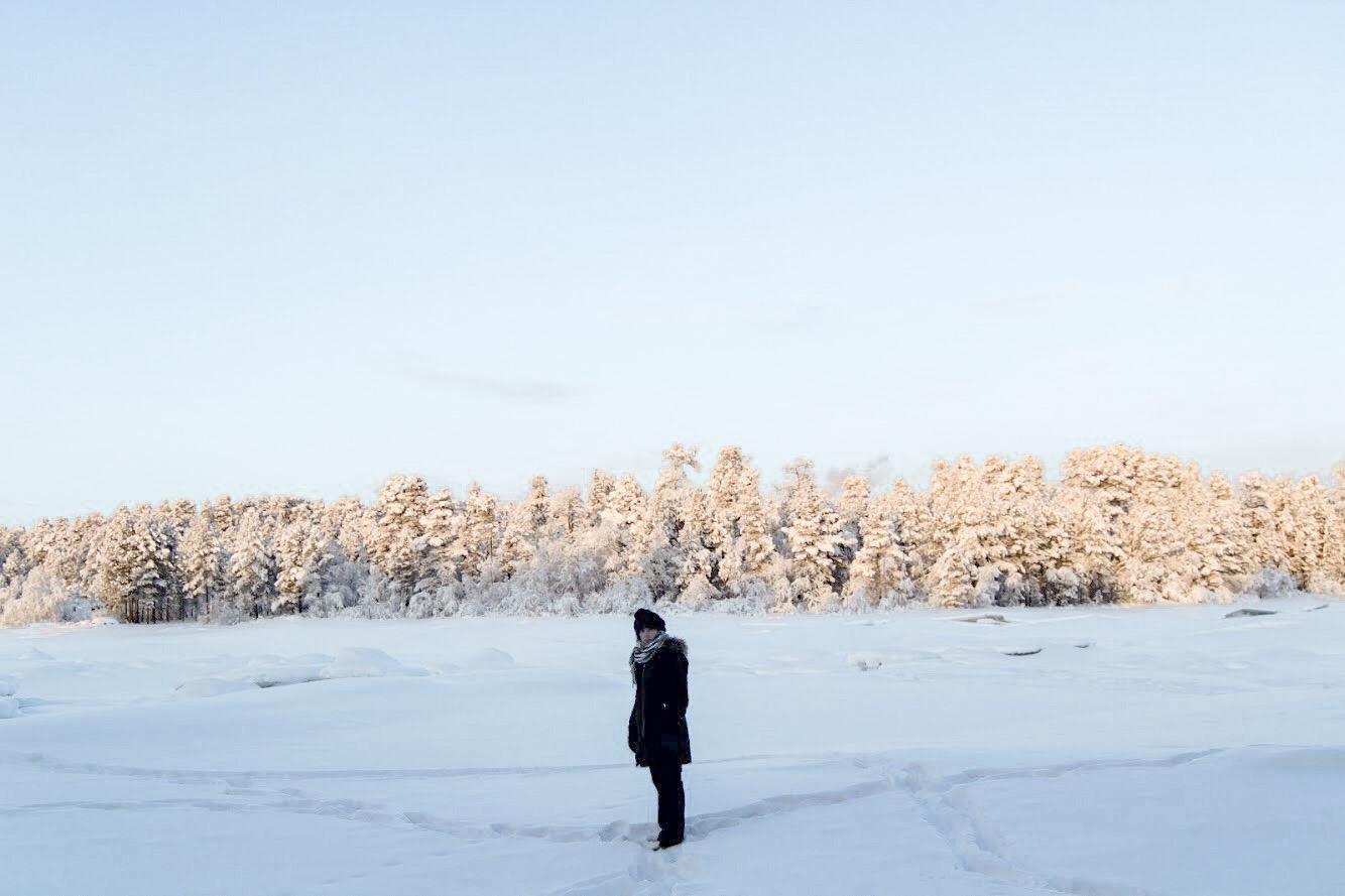 Mulher em Rio congelado em Inari - Inverno Finlândia comberto de neve