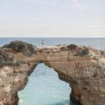 mulher em pé sobre o arco de albandeira com agua azul do mar abaixo no algarve em portugal