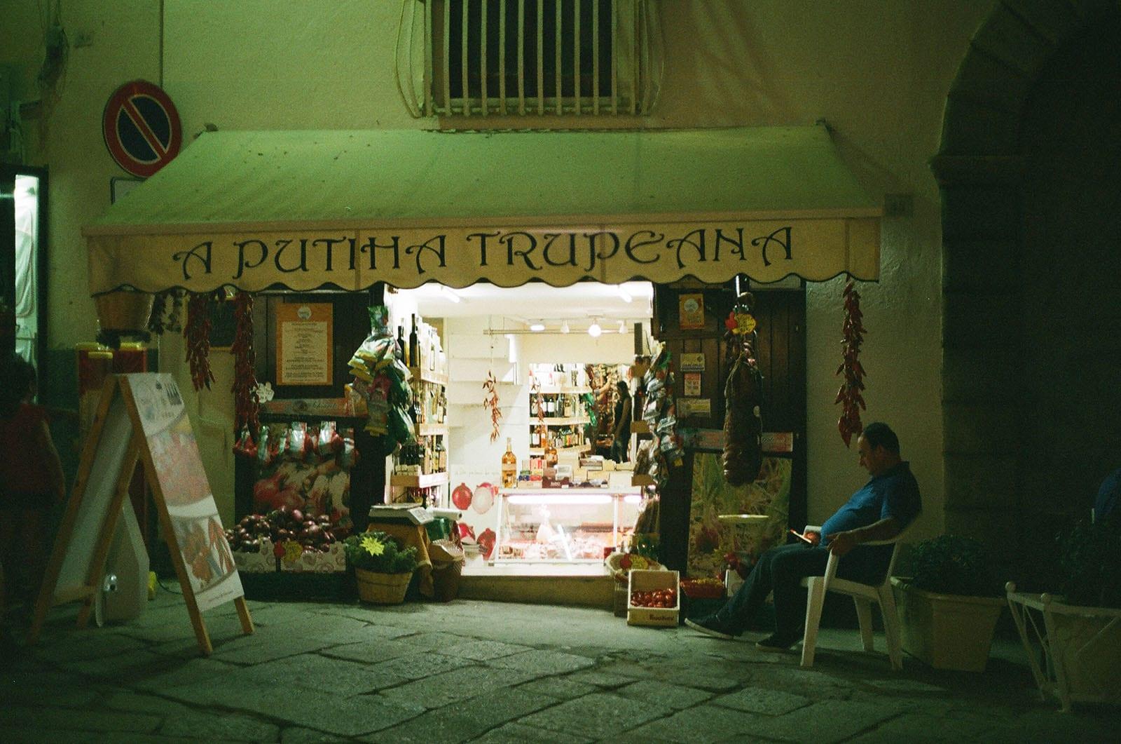 Loja em Tropea com homem sentado na frente
