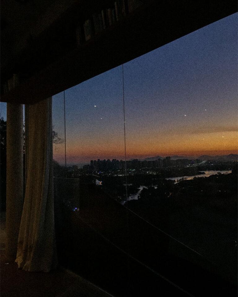por do sol visto por janela de vidro na casa do caio blat