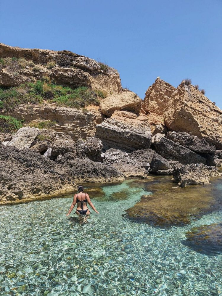 mulher andando na praia azul de favignana italia